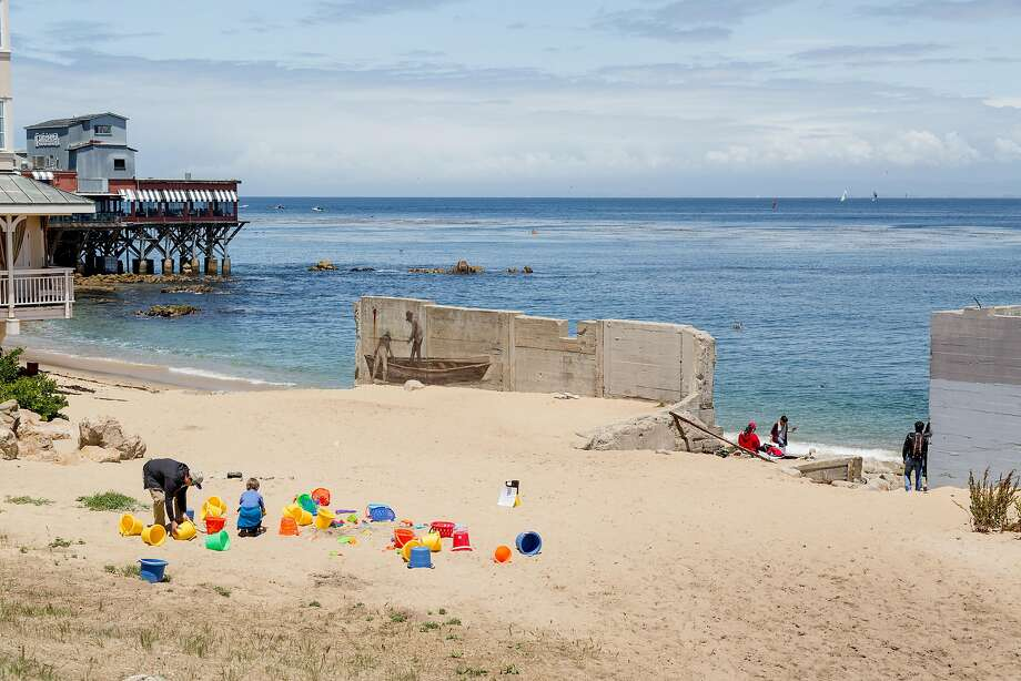 People enjoy a beach with a fishing mural along Cannery Row in Monterey, Calif., Saturday, May 24, 2016. Photo: Jason Henry, Special To The Chronicle