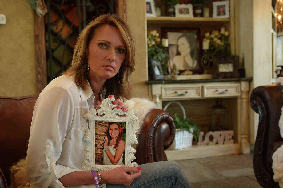 Kimberley Hess holds a photo of her daughter Cassidy at her home in The Woodlands. Cassidy was a student and varsity cheerleader at College Park. High School that committed suicide in December. Photo: Jerry Baker, Freelance