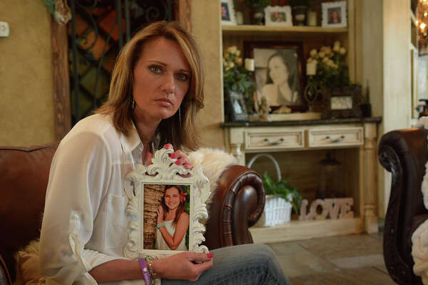 Kimberley Hess holds a photo of her daughter Cassidy at her home in The Woodlands. Cassidy was a student and varsity cheerleader at College Park. High School that committed suicide in December.