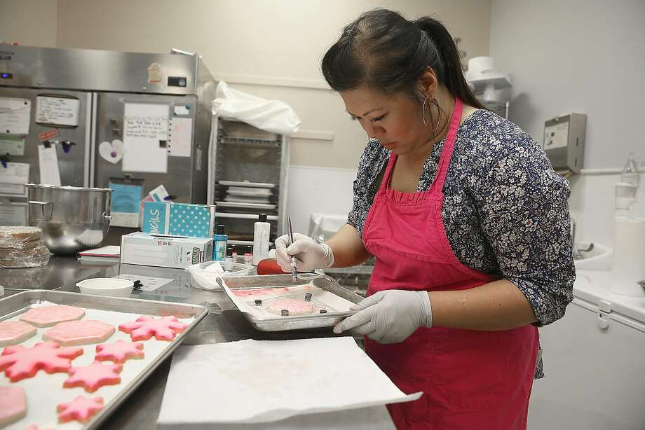 Annaleah Manipon uses an airbrush to spray pearl on a stenciled cookie on Thursday, May 26, 2016 in Clayton, Calif. Photo: Liz Hafalia, The Chronicle