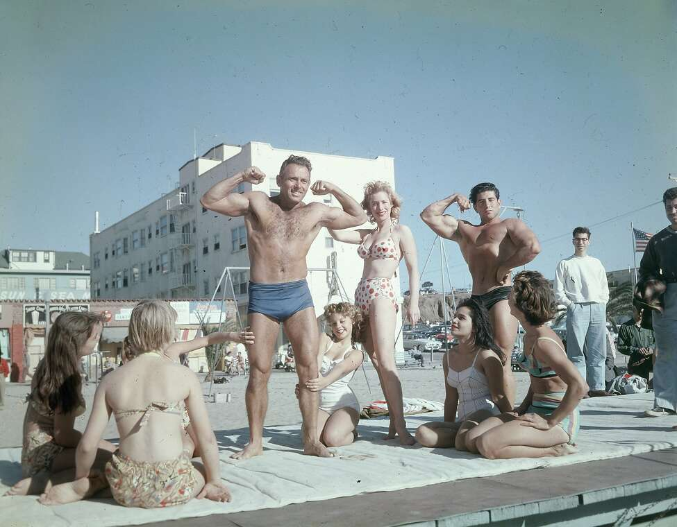 DeForrest Most, supervisor of the Muscle Beach area for Santa Monica Parks, flexing his muscles, Santa Monica, California, 1956.