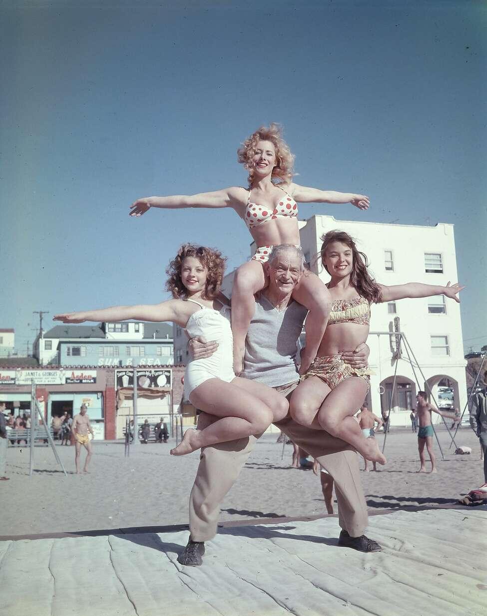 68-year-old Barney Frye lifts three women (L-R: Joan Greenman, Sherry Lee Evans, Kim Curtis) on the boardwalk, Muscle Beach, Santa Monica, California, 1956.