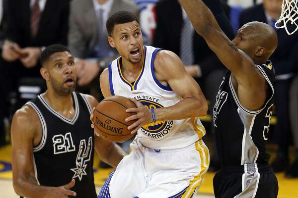 Golden State Warriors' Stephen Curry scores against San Antonio Spurs' David West and Tim Duncan in 1st quarter during NBA game at Oracle Arena in Oakland, Calif., on Thursday, April 7, 2016.