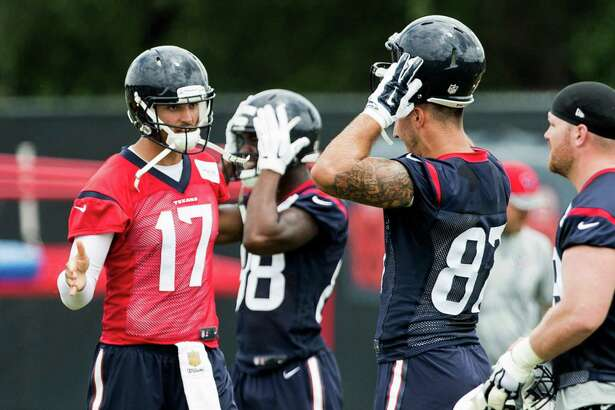 Houston Texans quarterbak Brock Osweiler (17) reaches out to slap hands with tight end C.J. Fiedorowicz (87) during OTAs at The Methodist Training Center on Tuesday, May 31, 2016, in Houston.