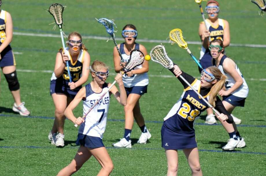 Staples sophomore Maeve Flaherty wins a draw against Mercy on April 10. Flaherty scored four goals on Friday in a 17-2 win at Stamford. Photo: Contributed Photo / Nelson Seo