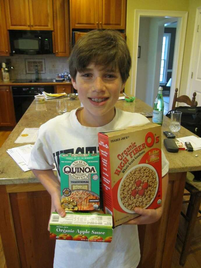 Thirteen-year-old Scott Yarmoff shows off a small sampling of the healthy and organic food his family's home is stocked with. Photo: Kirk Lang / Westport News