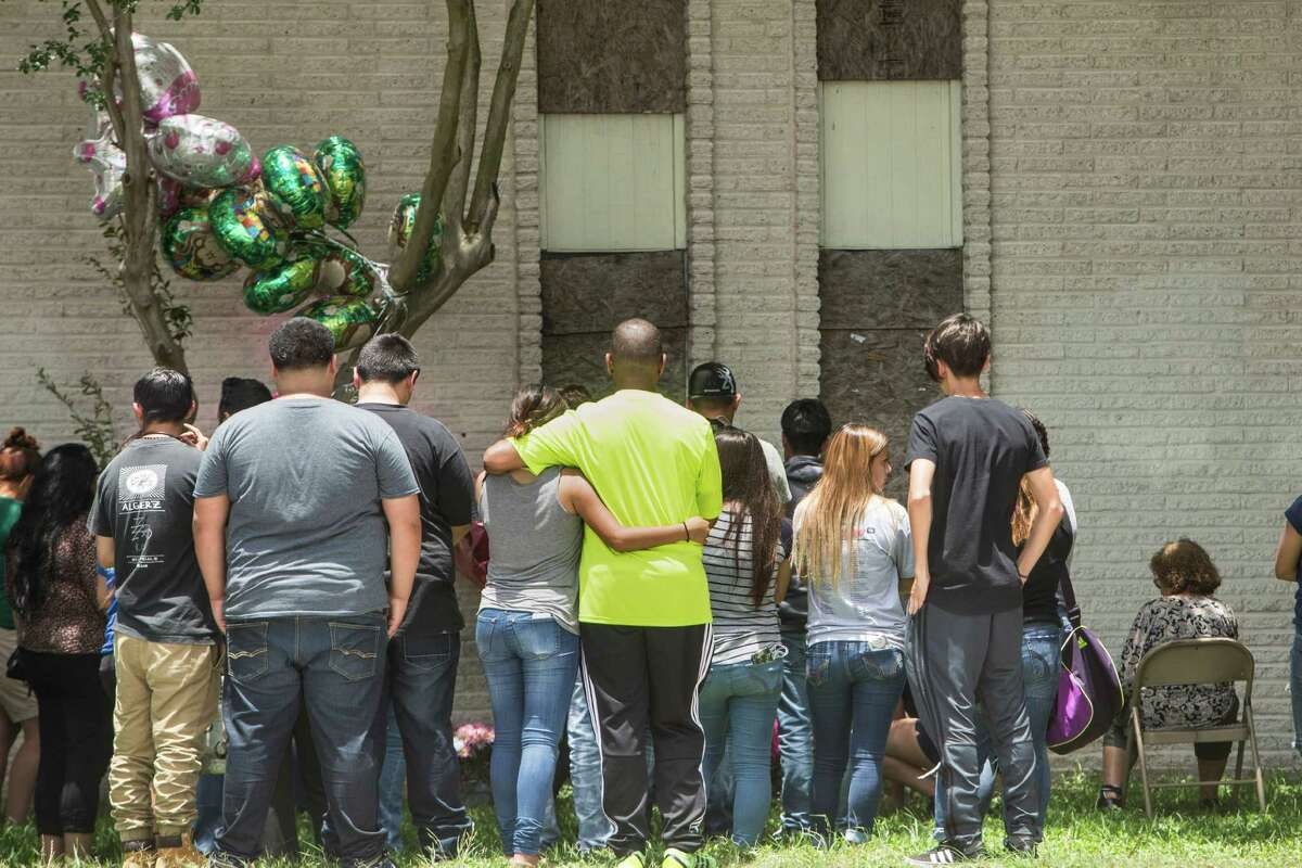 Mourners stand near a makeshift memorial for 15-year-old Karen Perez on Tuesday, May 31, 2016, in South Houston. It was early that morning when Tim Miller with Texas Equusearch confirmed Perez was found dead overnight in the abandoned apartment complex.