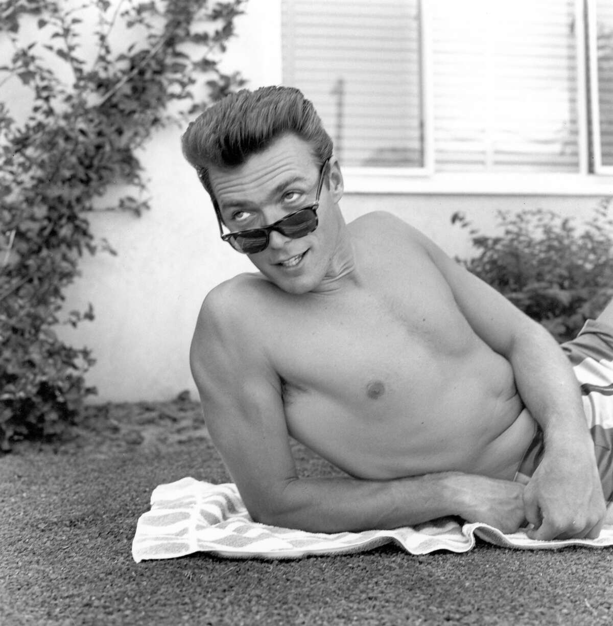 Actor Clint Eastwood lies on a towel and looks over his sunglasses at home on June 1, 1956 in Los Angeles.