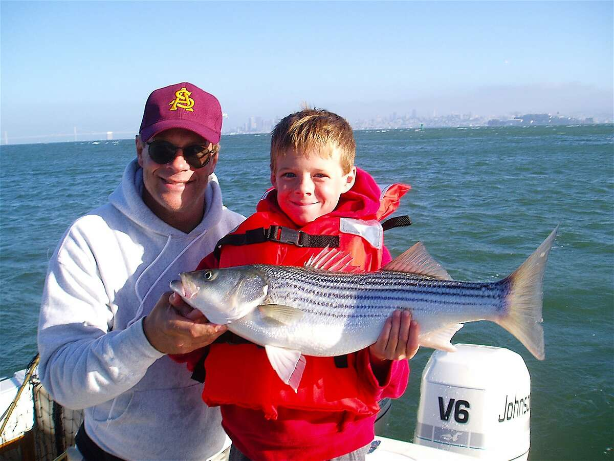 Kyle Catanese and dad Paul celebrate a bright striped bass taken near Angel Island in San Francisco Bay