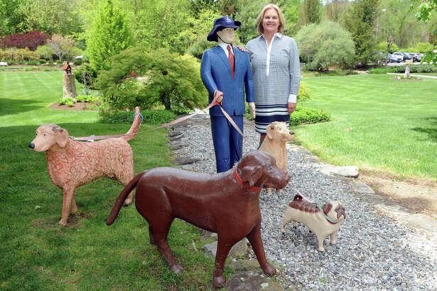 Helen Bickford, the new director of the Newtown Chamber of Commerce, poses with sculptures on display in Pleasance Garden, in Newtown, Conn. May 19, 2016.