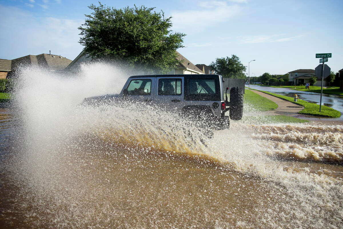 A jeep flies down a flooded street in the Rio Vista neighborhood Tuesday, May 31, 2016 in Richmond.