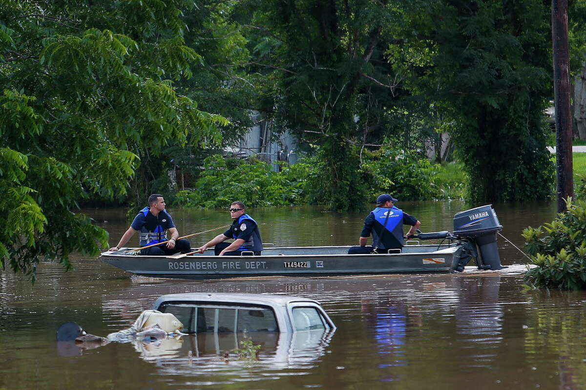 Rosenberg fire fighters motor past submerged cars and homes as they survey the damage along the Brazos River Tuesday, May 31, 2016 in Rosenberg.