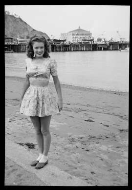 Norma Jeane Baker, future film star Marilyn Monroe (1926 - 1962), on the beach at Avalon, Santa Catalina Island, circa 1943. Her first husband James Dougherty was stationed on the island's boot camp at the time. In the background is the Avalon Casino.