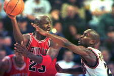 SEATTLE, UNITED STATES: Michael Jordan of the Chicago Bulls (L) looks to pass the ball as Seattle SuperSonics defender Gary Payton guards him during first quarter action in their game 03 February in Seattle, Washington. It was the first game between the two teams since the 1996 NBA Finals. Chicago won 91-84 with Jordan scoring 45 points. AFP PHOTO/Dan LEVINE (Photo credit should read DAN LEVINE/AFP/Getty Images)