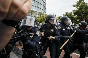 """Police officers with batons disperse anti-Trump protesters and Trump supporters following a campaign event for Donald Trump, presumptive Republican presidential nominee, not pictured, in San Diego, California, U.S., on Friday, May 27, 2016. Trump said he would rescind """"job-destroying"""" Obama administration environmental actions within 100 days of taking office and cancel a landmark international climate deal reached last year in Paris. Photographer: Patrick T. Fallon/Bloomberg"""