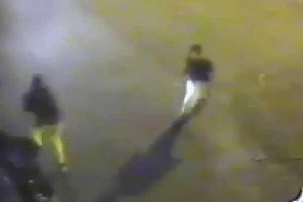 A screen grab of a video released by the Stamford Police Department shows a gunman, right, opening fire into a group of people early Saturday morning outside the La Quinta Inn and Suites on Harvard Avenue. Police are also looking for a person of interest, center, who is believed to be the gunman's accomplice.