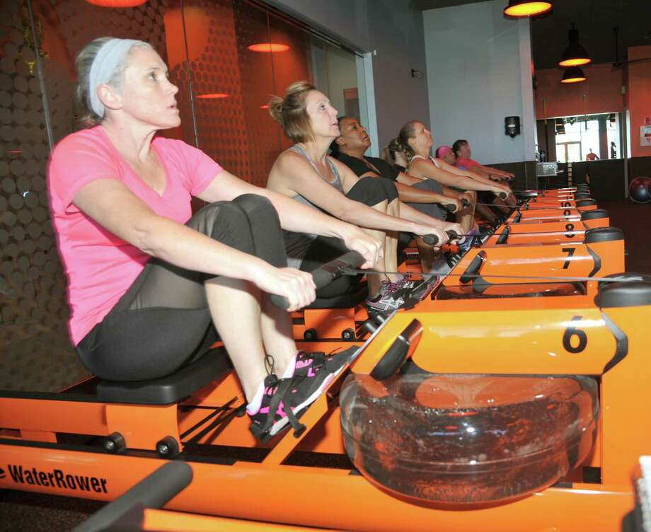 "Susan Finnell works out on a rowing machine at Orangetheory Fitness, one of a cluster of businesses that have opened at the Towne Lake Boardwalk mixed-use development, which includes boat docks, an office park and a music pavilion. ""It's just where everyone wants to be,"" says owner Jose Malaga. Photo: Eddy Matchette, Freelance / Freelance"