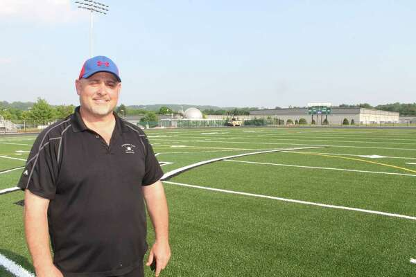 New Milford High School Athletic Field Committee member Douglas Skelly inspects progress on the school's new artificial turf fields on Saturday.