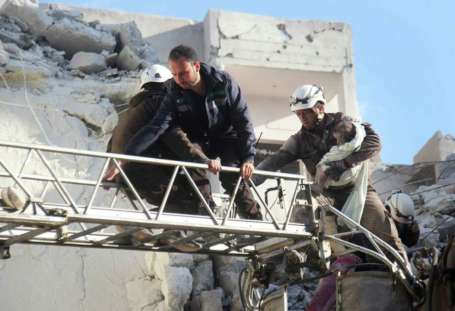 Members of the Syria Civil Defense, a Western-funded group, evacuate a toddler from the rubble of buildings near the National Hospital on Tuesday in Idlib, Syria, after a barrage of airstrikes. Photo: OMAR HAJ KADOUR, Stringer / AFP or licensors