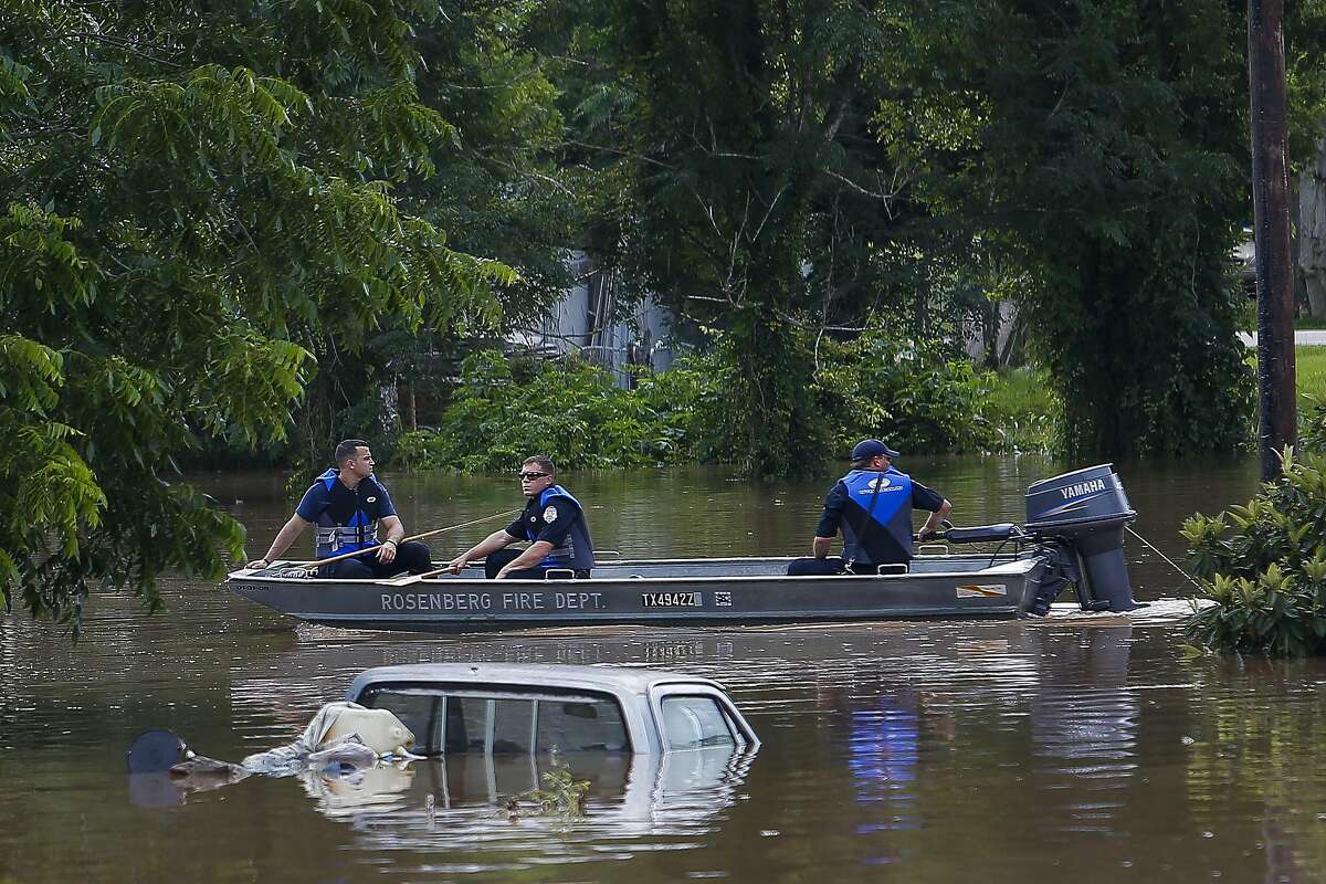 Rosenberg fire fighters motor past submerged cars and homes as they survey the damage along the Brazos River Tuesday, May 31, 2016 in Rosenberg. ( Michael Ciaglo / Houston Chronicle )