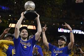 Golden State Warriors' Klay Thompson (11) lifts the NBA Western Conference championship trophy in the air as teammate Stephen Curry (30) celebrates on Monday, May 30, 2016, at Oracle Arena in Oakland, Calif. (Jose Carlos Fajardo/Bay Area News Group/TNS)