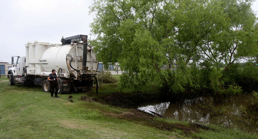 A crew with the FlowFect Company works Tuesday May 31, 2016 to to clean up an oil spill that took place near the Lakeshore Estates neighborhood in Lytle, Texas. Johnny Melancon, president of FlowFect, said lightning stuck an oil storage tank Sunday causing around 15 to 20 barrels of oil to leak and flow with rainwater into the neighborhood and a nearby pond. The crew is using a special soap to emulsify the oil.