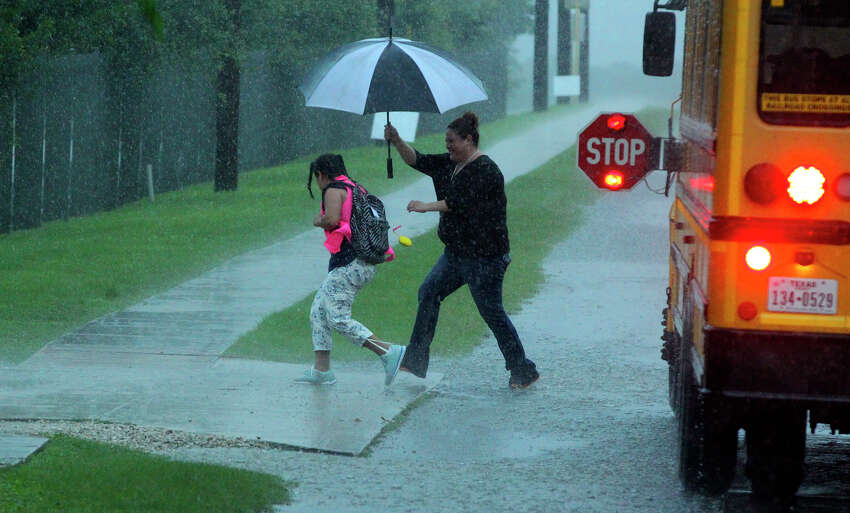 A woman helps a girl dash through the pouring rain after getting off a school bus Tuesday May 31, 2016 in the 13000 block of Jones Maltsberger Road.. An afternoon storm swept through the San Antonio area with lightning strikes causing power outages in some areas.