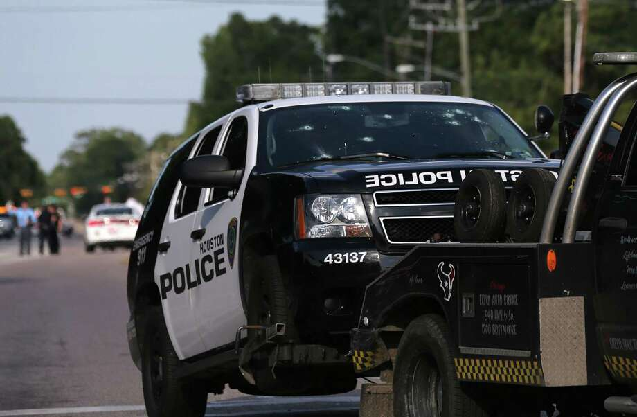 A Houston Police Deptartment SUV that was hit with bullets 21 times is removed Sunday from an investigation scene on Memorial near Wilcrest. Two people, including a suspect, were killed in the shootout. Three other people and two constable's deputies were injured. (Elizabeth Conley / Houston Chronicle) Photo: Elizabeth Conley, MBI / Houston Chronicle