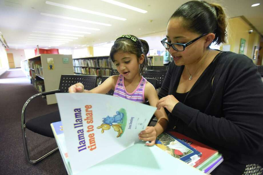 """Serenity Martinez, 5, and her mother, Denise Martinez, read though the children's book """"Llama Lama, Time to Share,"""" during the kickoff of the 2016 San Antonio Public Library Mayor's Summer Reading Club and Summer Reading Program at the Central Library on Tuesday, May 31, 2016. Mayor Ivy Taylor spoke about her own childhood reading habits, when her parents would allow her to read during meals. Serenity signed up for the club. Photo: Billy Calzada, Staff / San Antonio Express-News / San Antonio Express-News"""