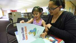 "Serenity Martinez, 5, and her mother, Denise Martinez, read though the children's book ""Llama Lama, Time to Share,"" during the kickoff of the 2016 San Antonio Public Library Mayor's Summer Reading Club and Summer Reading Program at the Central Library on Tuesday, May 31, 2016. Mayor Ivy Taylor spoke about her own childhood reading habits, when her parents would allow her to read during meals. Serenity signed up for the club."