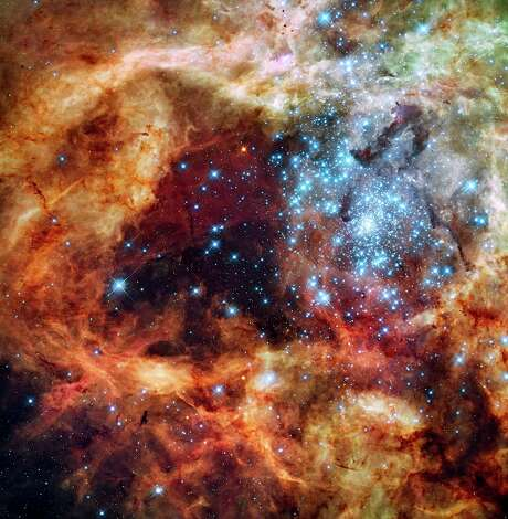 Image from Houston Symphony's Cosmos: An HD Odyssey. The spectacular 30 Doradus Nebula is one of the most prolific star birth regions known. Here two star clusters are gradually merging triggering the birth of hundreds of brilliant blue supermassive stars, many of which are over a hundred times more massive than our Sun. The nebula is situated some 170,000 light-years away in the Large Magellanic Cloud, a satellite galaxy of our own galaxy. Photo: NASA / ESA / STScI &E. Sabbi