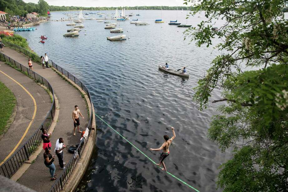 People practice on a slack line while others kayak, paddle board and canoe in Lake Calhoun in Minneapolis, Photo: JENN ACKERMAN, STR / NYTNS