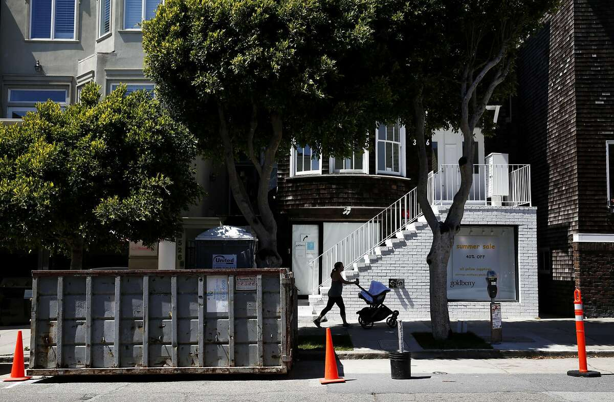 A woman pushes a stroller past the construction permitted area outside 3516 Sacramento St. in San Francisco, California, on Tuesday, May 31, 2016.