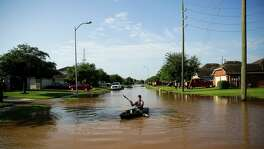Anthony Perry kayaks down his street in the flooded Rio Vista neighborhood Tuesday in Richmond.