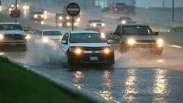 Cars splash through deep water accumulating fast on the access road to Loop 410 at Broadway during a heavy downpour in the area on May 31, 2016.
