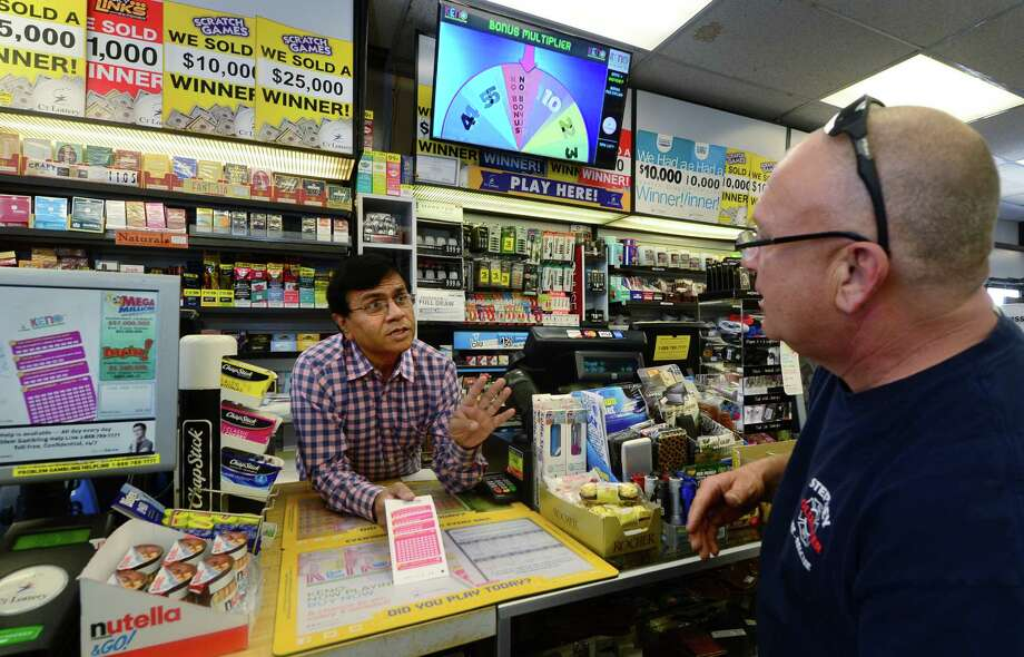 Upen Shah, owner of Crossroads Card & Gift, shows customers, including Jim Mace, how to play the Connecticut Lottery's new Keno game in his Norwalk store Wednesday, April 20, 2016. Crossroads is one of only two stores in Fairfield County offering Keno as the state of Connecticut begins to roll out the new game started in April. Photo: Erik Trautmann / Hearst Connecticut Media / (C)2016, The Connecicut Post, all rights reserved