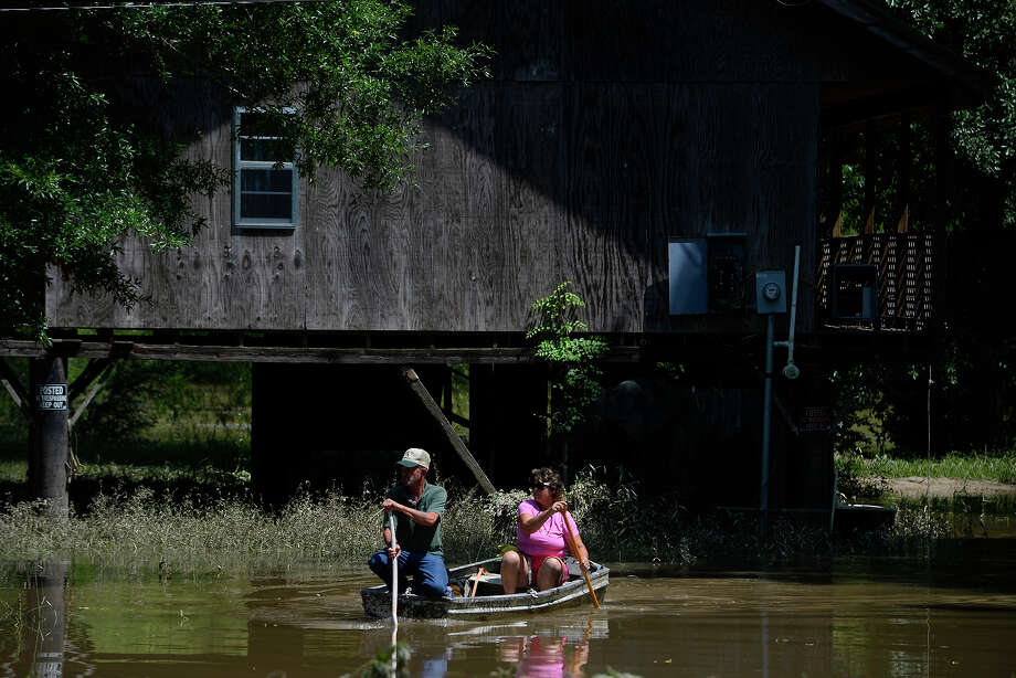 Lonnie and Connie Etie paddle a boat away from a house on the Neches River in Tyler County on Tuesday. The house, built on stilts, has stayed dry, but flood waters have surrounded it.  Photo taken Tuesday 5/31/16 Ryan Pelham/The Enterprise Photo: Ryan Pelham / ©2016 The Beaumont Enterprise/Ryan Pelham