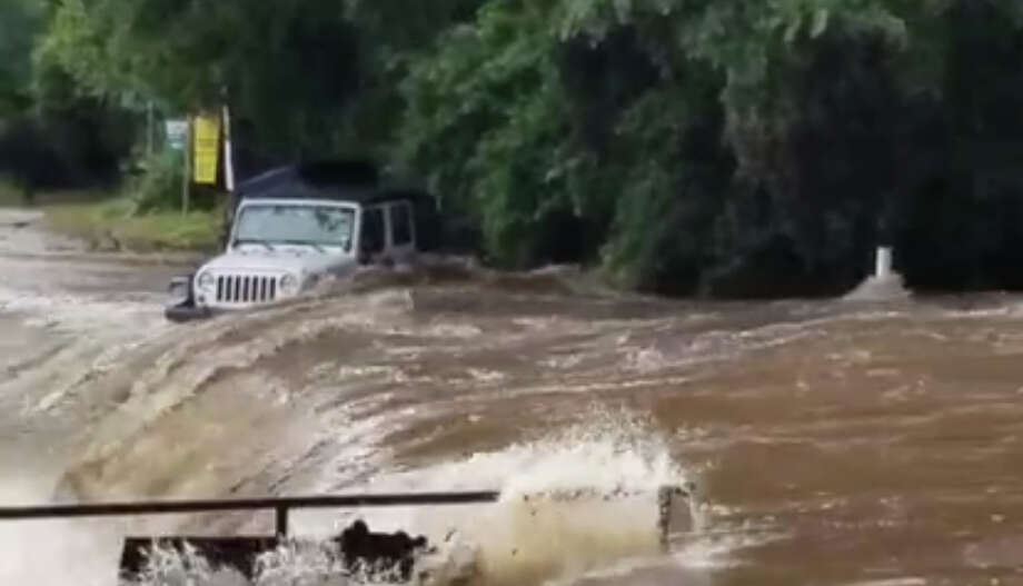 Video taken at the first crossing on River Road in New Braunfels, Texas, near Jerry's Rentals, shows a Jeep swept off the road by high water and downstream. Photo: Kim Jacob/Facebook