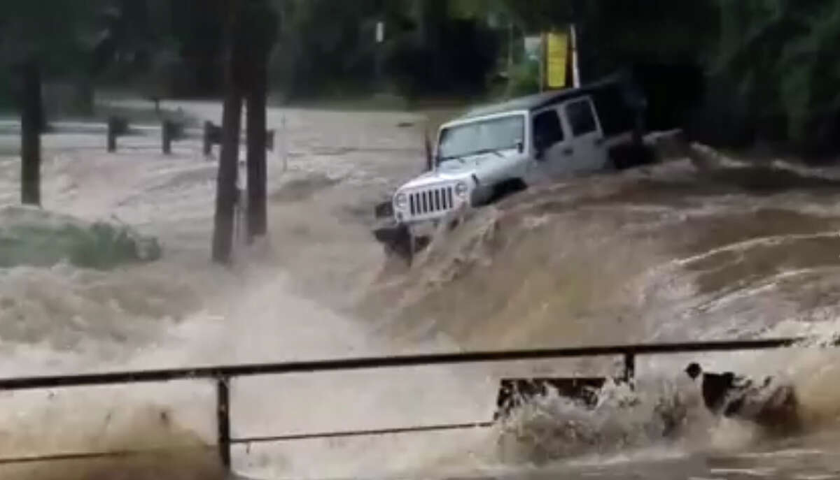 Video taken at the first crossing on River Road in New Braunfels, Texas,near Jerry's Rentals, shows a Jeep swept off the road by high water and downstream.