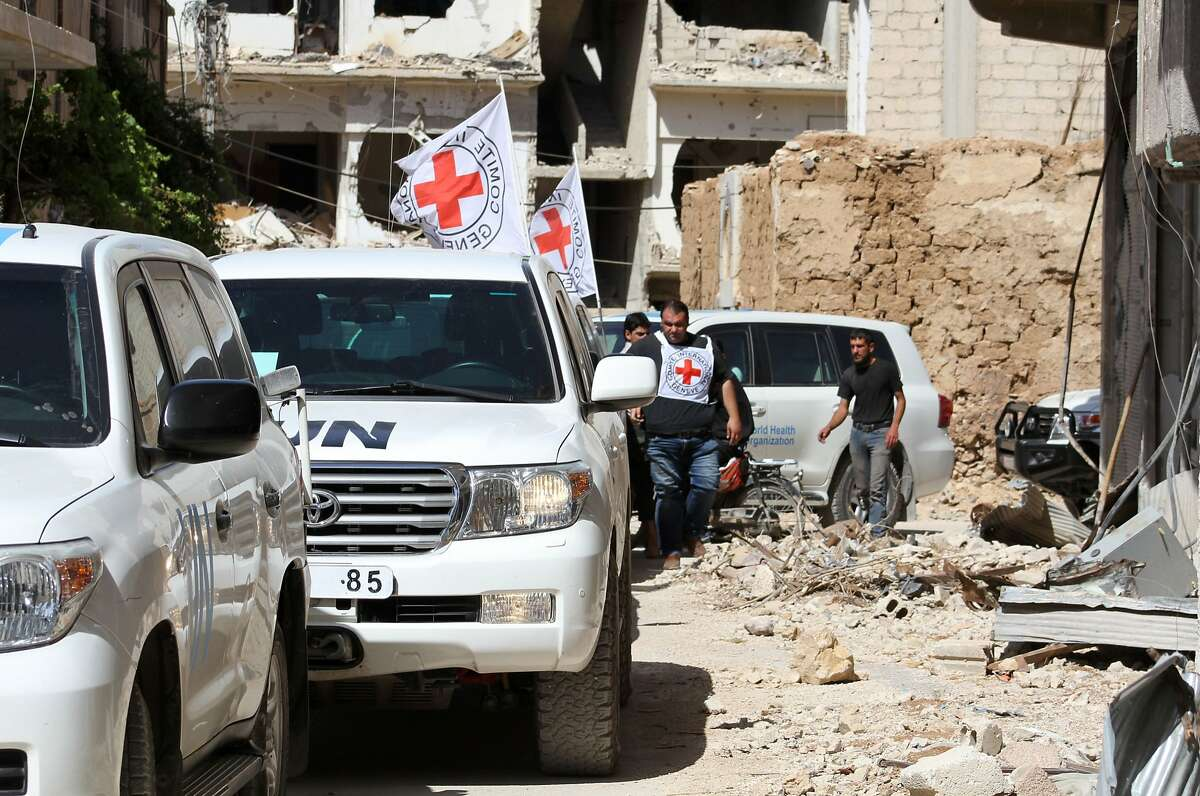 Vehicles of the International Committee of the Red Cross (ICRC) and the United Nations wait on a street after an aid convoy entered the rebel-held Syrian town of Daraya, southwest of the capital Damascus, on June 1, 2016. A humanitarian aid convoy entered Daraya, the Red Cross said, in the first such delivery since a regime siege began in 2012. But the opposition said only medical supplies were in the delivery and British charity Save the Children said it was