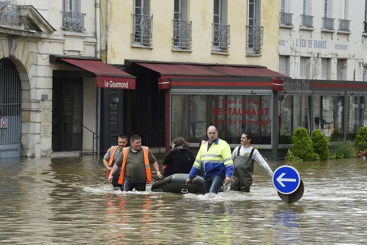 Municipal employess pull a small boat transporting inhabitants through a flooded street on June 1, 2016 in Nemours, southeast of Paris. Torrential downpours have lashed parts of northern Europe in recent days, leaving four dead in Germany, breaching the banks of the Seine in Paris and flooding rural roads and villages.  AFP PHOTO / DOMINIQUE FAGETDOMINIQUE FAGET/AFP/Getty Images