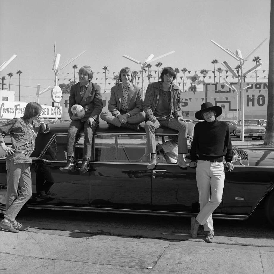"Superstar group ""Buffalo Springfield"" pose for a portrait sitting on a car in 1966 in Los Angeles, 1966. (L-R) Bruce Palmer, Dewey Martin, Stephen Stills, Neil Young, Richie Furay. Photo: Earl Leaf/Michael Ochs Archive/Getty Images"