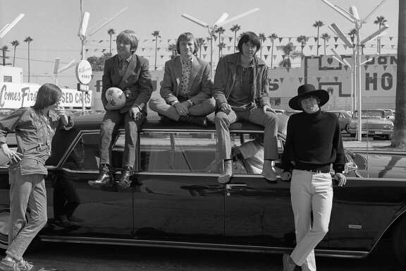 """Superstar group """"Buffalo Springfield"""" pose for a portrait sitting on a car in 1966 in Los Angeles, 1966. (L-R) Bruce Palmer, Dewey Martin, Stephen Stills, Neil Young, Richie Furay."""