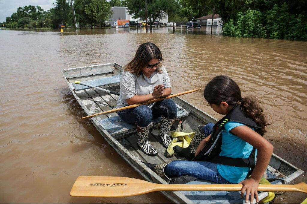 A woman and a girl travel through the flooded town of Booth, Texas on Wednesday, June 1, 2016. Residents and local wildlife could be seen attempting to flee the rising flood waters. Photo: Michael Ciaglo/Houston Chronicle