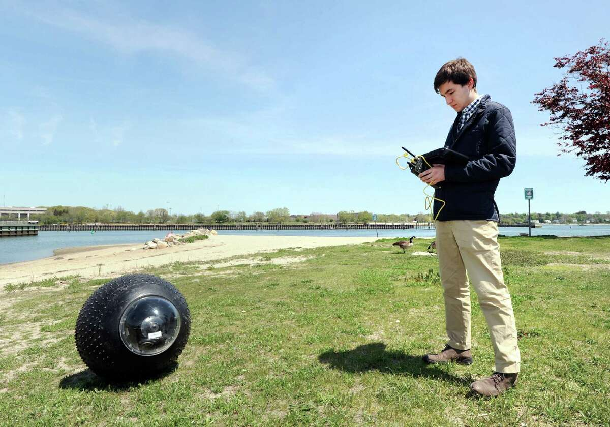 GuardBot Inc. Engineer Philippe Vibien controls a GuardBot, foreground, using a wireless remote control device at Southfield Park in Stamford. GuardBots are spherical amphibious robotic vehicles.