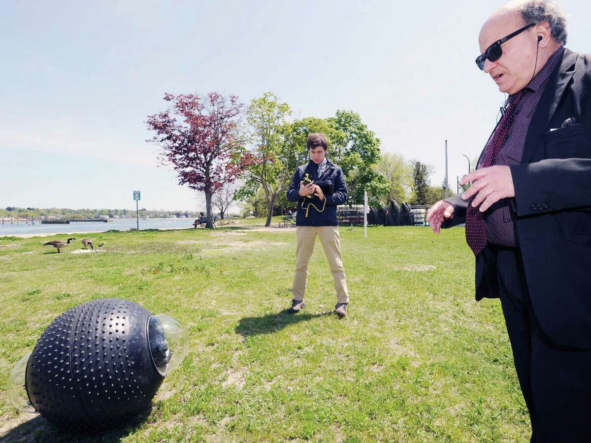 Engineer Philippe Vibien, left manuevers a GuardBot with a remote control device. At right, GuardBot Inc. President Peter Muhlrad looks on. They were testing the spherical amphibious robotic vehicle at Southfield Park in Stamford.