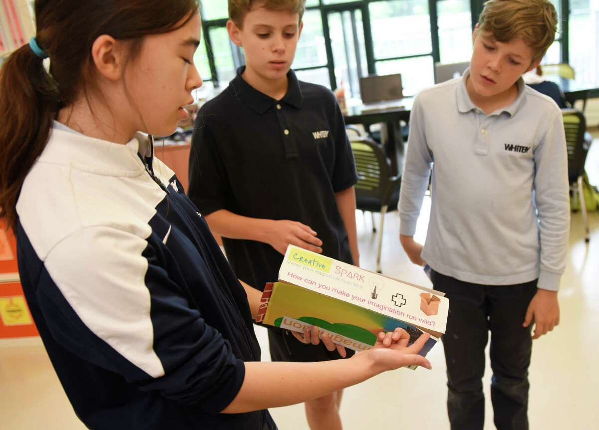 Seneca Schmitz, left, Alex Resnick, center, and Luca Hoskin show their group's branding and packaging project, Creative Spark, during the sixth-grade Design class at Whitby School in Greenwich, Conn. Tuesday, May 24, 2016. Students came up with an original product and designed the product packaging and advertising for the product.