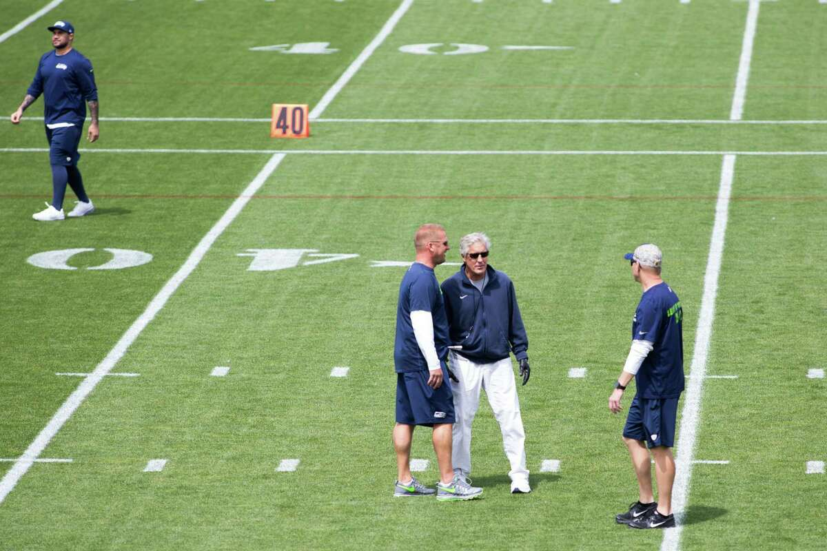 Seahawks head coach Pete Carroll talks with coaches during organized team activities practice at Virginia Mason Athletic Center in Renton on Wednesday, June 1, 2016.