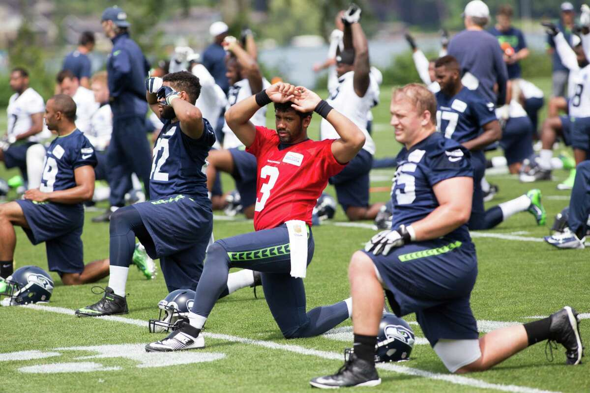 Seahawks quarterback Russell Wilson stretches during organized team activities practice at Virginia Mason Athletic Center in Renton on Wednesday, June 1, 2016.