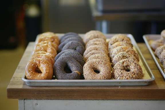 A variety of bagels (salted {l to r}, poppy seed, sesame and everything) sit on a tray on a counter at Marla Bakery on Tuesday, December 1,  2015 in San Francisco, Calif.